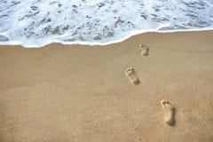 Les empreintes de pas dans le sable vont à la mer Images libres de droits