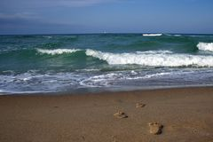 Les empreintes de pas dans le sable vont à la mer Image stock