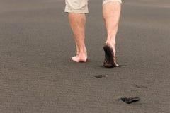 Les empreintes de pas des hommes en sable volcanique Photographie stock libre de droits