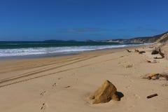 Les empreintes de pas et les voies de voiture dans le sable le long de l'arc-en-ciel échouent des falaises photo stock