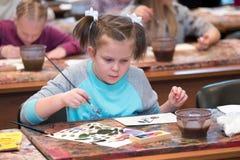 Les enfants âgés 6-9 ans s'occupent de l'atelier gratuit de dessin pendant la journée 'portes ouvertes' à l'école d'aquarelles Photos libres de droits