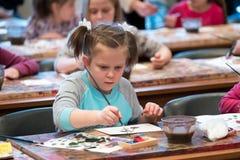 Les enfants âgés 6-9 ans s'occupent de l'atelier gratuit de dessin pendant la journée 'portes ouvertes' à l'école d'aquarelles Image libre de droits