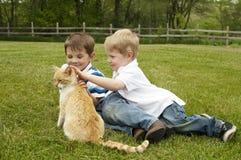Les enfants adoucissent et sorte aux animaux Photo stock