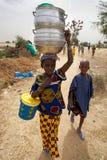 Les enfants africains marchant dans la campagne, une jeune fille est carryin photographie stock libre de droits