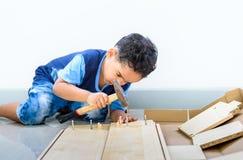 Les enfants aident les parents à la table de salle à manger d'assemblée, un meuble photographie stock