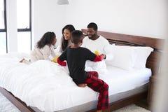 Les enfants amenant des parents d?jeunent dans le lit pour c?l?brer le jour ou l'anniversaire de p?res de jour de m?res image stock