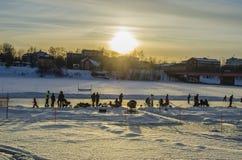 Les enfants apprécient le jeu sur la rivière congelée avec leur famille photos libres de droits