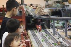 Les enfants apprécient les trains modèles Photos stock