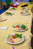Les enfants apprennent à faire cuire des spaghetti dans des cuisiniers d'école pour de petits enfants Photographie stock libre de droits