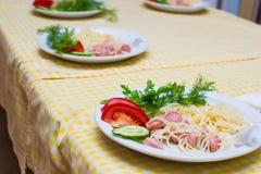 Les enfants apprennent à faire cuire des spaghetti dans des cuisiniers d'école pour de petits enfants Image libre de droits
