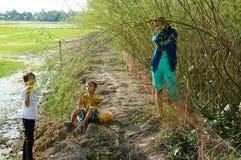 Les enfants asiatiques, bong dien dien, sesbana de Sesbania, delta du Mékong photos stock