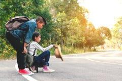 Les enfants asiatiques heureux se baladent à l'arrière-plan de route et de forêt Image libre de droits