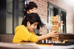 Les enfants asiatiques jouent le jeu en bois de piles de bloc ensemble photos stock