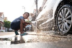 Les enfants asiatiques utilisent le tuyau de l'eau à la voiture de lavage photos libres de droits