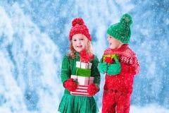 Les enfants avec des cadeaux de Noël en hiver se garent dans la neige Photos stock