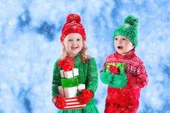 Les enfants avec des cadeaux de Noël en hiver se garent dans la neige Images libres de droits