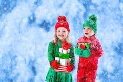 Les enfants avec des cadeaux de Noël en hiver se garent dans la neige Photos libres de droits
