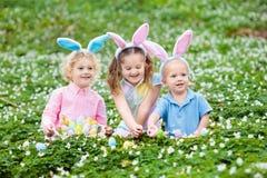 Les enfants avec des oreilles de lapin sur l'oeuf de pâques chassent Images libres de droits