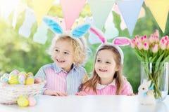 Les enfants avec des oreilles et des oeufs de lapin sur l'oeuf de pâques chassent Image stock