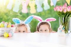 Les enfants avec des oreilles et des oeufs de lapin sur l'oeuf de pâques chassent Photographie stock libre de droits