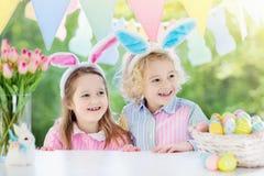 Les enfants avec des oreilles et des oeufs de lapin sur l'oeuf de pâques chassent Photos libres de droits