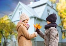 Les enfants avec l'érable d'automne part au-dessus de la maison dehors images stock