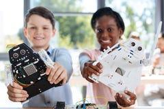 Les enfants avec le robot modèle le sourire à l'appareil-photo Images stock