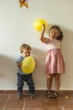 Les enfants avec les ballons jaunes ayant l'amusement dans les enfants font la fête Images libres de droits