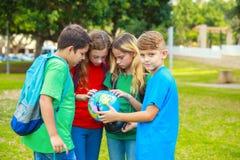 Les enfants avec un globe apprennent la géographie Photographie stock libre de droits