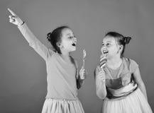 Les enfants avec les visages curieux se dirigent avec des sucreries sur le fond vert Confiserie et concept d'enfance Soeurs avec Images stock