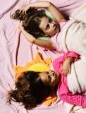 Les enfants avec les visages rêveurs et les cheveux lâches se situent dans le lit photos libres de droits