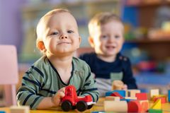 Les enfants caucasiens de sourire heureux jouent avec les jouets éducatifs dans la crèche photographie stock