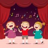 Les enfants chantent avec un microphone sur l'étape Photographie stock