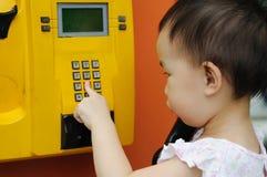 Les enfants chinois effectuent un appel téléphonique Photos libres de droits