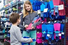 Les enfants choisissent des ailerons de bain dans la boutique de sports Image stock