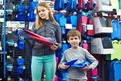 Les enfants choisissent des ailerons de bain dans la boutique de sports Photos stock