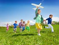Les enfants courants actifs avec le garçon tenant l'avion jouent Photographie stock libre de droits