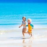 Les enfants courent et jouent sur la plage tropicale Image libre de droits