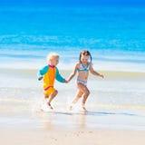 Les enfants courent et jouent sur la plage tropicale Images stock