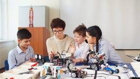 Les enfants curieux apprennent la programmation utilisant des ordinateurs portables sur les classes hors programme
