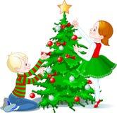 Les enfants décorent un arbre de Noël Image libre de droits