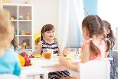 Les enfants dînent dans le jardin d'enfants photos libres de droits