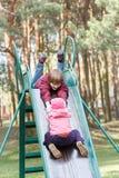 Les enfants d'enfant de mêmes parents jouent sur la glissière de terrain de jeu Photographie stock