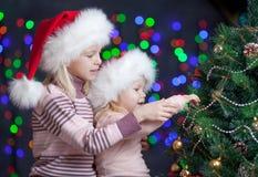 Les enfants dans des chapeaux du père noël s'approchent de l'arbre de Noël Image stock