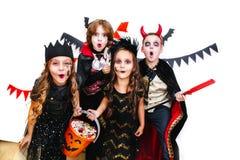 Les enfants dans des costumes de Halloween montrent les visages drôles Image libre de droits