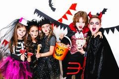 Les enfants dans des costumes de Halloween montrent les visages drôles Photo libre de droits