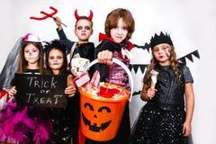 Les enfants dans des costumes de Halloween montrent les visages drôles Images libres de droits