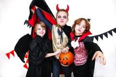 Les enfants dans des costumes de Halloween montrent les visages drôles Photo stock