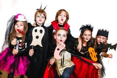 Les enfants dans des costumes de Halloween montrent les visages drôles sur la partie Photo stock