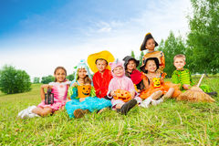 Les enfants dans des costumes de Halloween s'asseyent ensemble Photographie stock